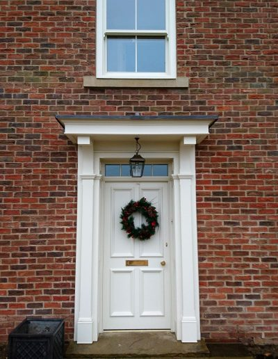 Panelled door with wood portico surround