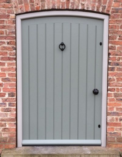 Wide boarded door with curved head